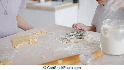 Child helping mother to cook biscuits using dough and flour...