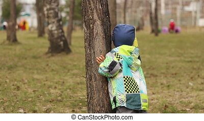Child hiding behind a tree
