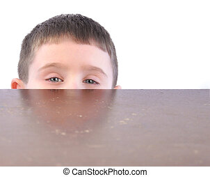 Child Hiding Behind Kitchen Table - A little boy is hiding...