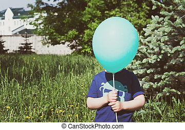 Child hiding behind the balloon