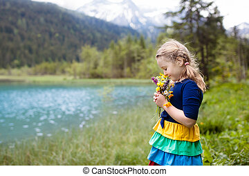 Child hiking in flower field at mountain lake - Child hiking...
