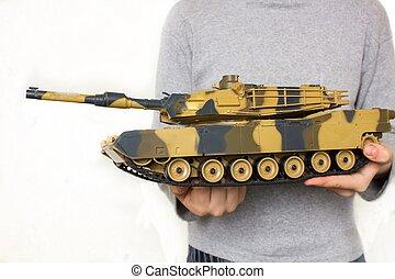 Child holding a big toy tank