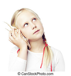 Child holding a shell to his ear, communication concept