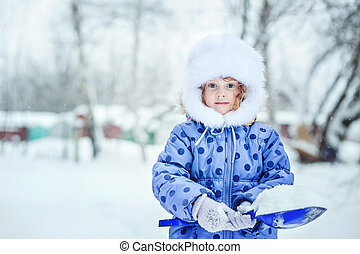 Child holding a shovel, playing outdoors in winter.