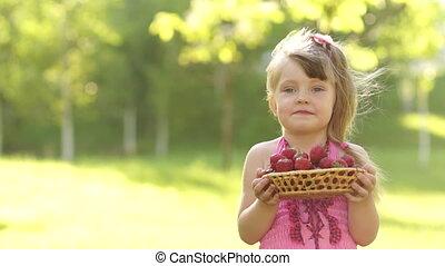 Child holding basket of strawberrie