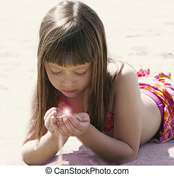 Child holding beach sand