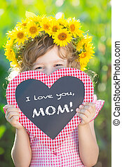 Child holding blackboard against green background. Spring family holiday concept. Mother's day