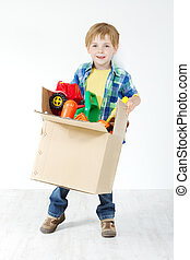 Child holding cardboard box packed with toys. Moving and growing concept