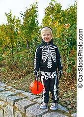 child holding Halloween pumpkin Jack O'Lantern basket