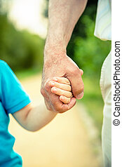 Child holding hand of senior man in the nature