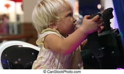 child holding joystick and playing on the machine on...