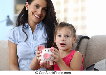 Portrait of attractive little kid with pink piggy bank. Smiling mother looking at camera with gladness. Amused daughter shaking thrift-box. Money savings concept