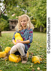 child holding pumpkins in autumn garden