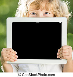 Child holding tablet PC - Happy child holding tablet PC...
