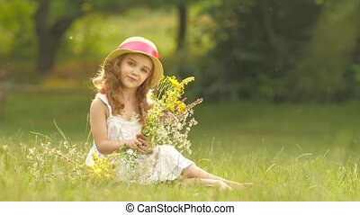 Child holds a bouquet of wildflowers in her hands, she smells them and smiles