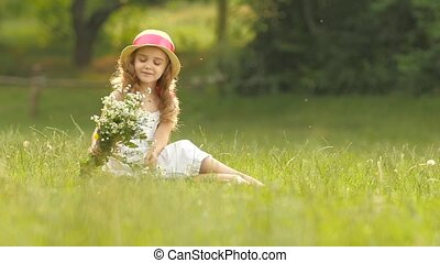 Child holds a bouquet of wildflowers in her hands, she smells them and smiles. Slow motion