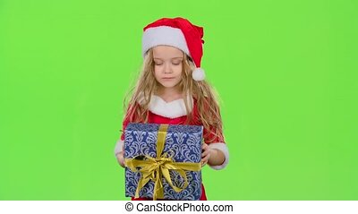 Child holds a gift box in his hands and does not know what's...