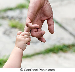 child holds the finger of a hand of the father