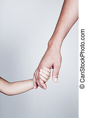 Child holds the hand of father