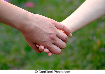Child holds the hand of the mother on field