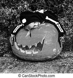 child hugging huge Halloween pumpkin Jack O'Lantern