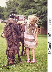 child hugging little brown horse
