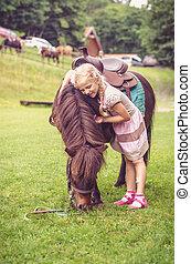 child hugging little brown pony