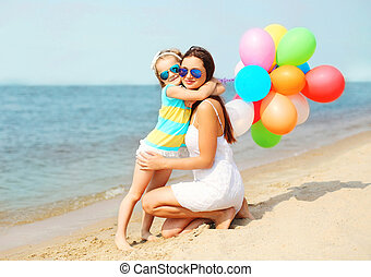 Child hugging mother with colorful balloons on beach near sea