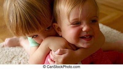 Child hugging sibling at home - Kid tightly embracing little...