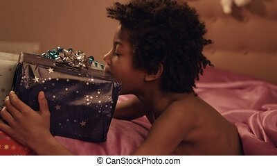 Child hugs gift boxes. Playing afro boy hugs present....
