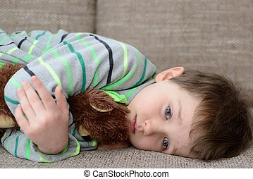 child hugs his  teddy bear and lying on the sofa