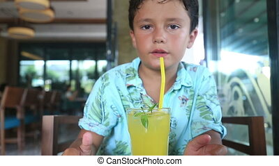 child  in a cafe drinking lemonate