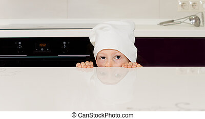 Child in a chefs toque hiding behind a counter