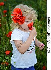 child in a corn poppy field