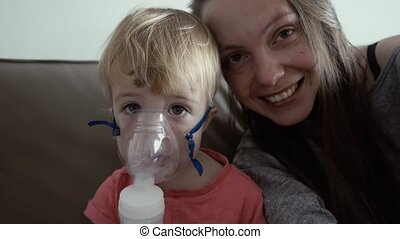 Child in a mask nebulizer. Mother hugs a sick son