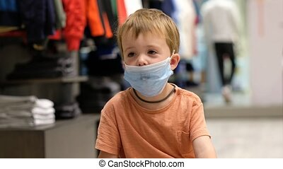 Child in a protective mask in a store - Kid boy in a ...