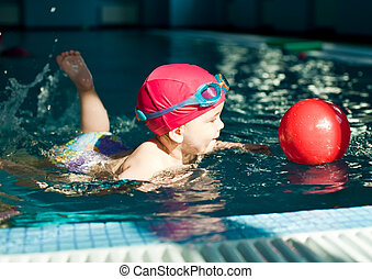 Child in a swimming pool - Little girl playing with red ball...
