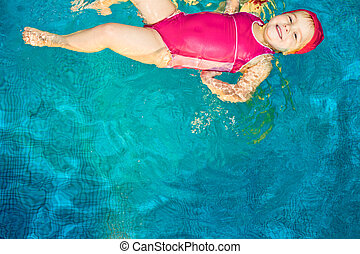 Child in a swimming pool - Cute little girl swimming in a...