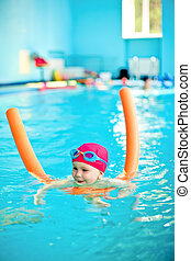 Child in a swimming pool - Happy little girl learning to...