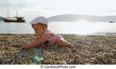 child in a white cap sits on a pebble on the beach of...