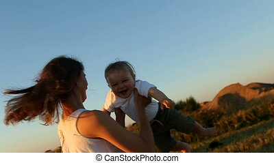 child in a white t-shirt spinning in the hands of a young mother in a white dress