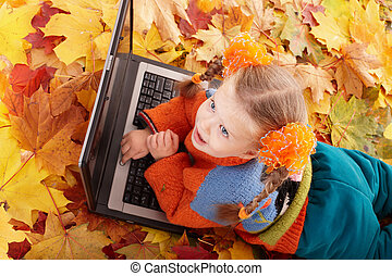 Child in autumn orange leaves with laptop.