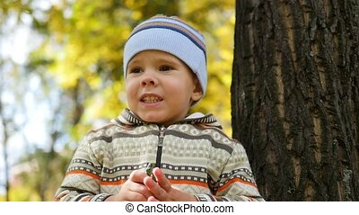 Child in autumn Park having fun playing and laughing ,...