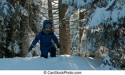 child in blue sports suit rolled head over heels from snow...