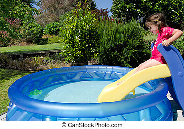 Child in children inflatable pool - Child (girl) slides on a...