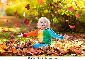 Child in fall park. Kid with autumn leaves.