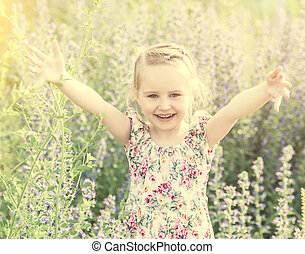 child in field among flowers and herbs, smiling