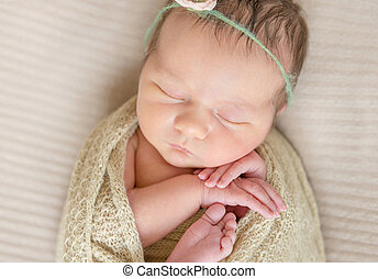 Small child in a flowery hairband sleeping tight covered and wrapped in a scarf, topview