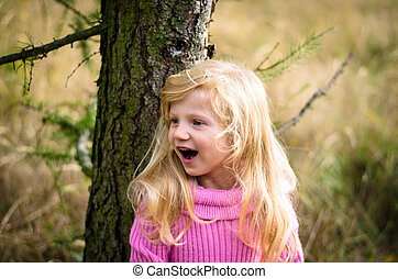 child in forest smiling