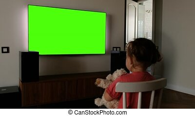 Child in front of a green screen TV